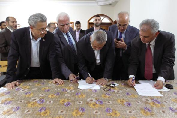 Head of Hamas government Ismail Haniyeh (C) and senior Fatah official Azzam Al-Ahmed (2nd L) sign the reconciliation agreement. Gaza City April 23, 2014.